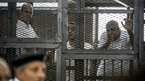 Peter Greste (left) and his colleagues Mohamed Fadel Fahmy and Baher Mohamed listen to the verdict from inside the defendants' cage. Photo: AFP