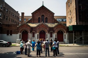 Former parishioners of Our Lady of Queen of Angels, which closed in 2007, praying this month in East Harlem. Credit Todd Heisler/The New York Times