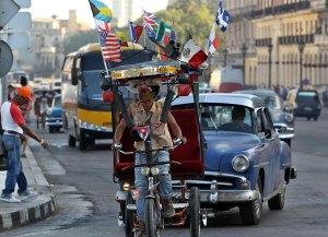 Un bicitaxi adornado con varias banderas, entre ellas una de Estados Unidos, circula por una calle de La Habana el 31 de marzo de 2015.