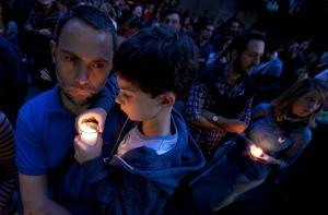 En esta imagen de archivo del lunes 16 de noviembre de 2015, un hombre sostiene a un niño en brazos ante la embajada francesa en Ciudad de México durante una vigilia por las víctimas de los atentados terroristas en París. (AP Foto/Marco Ugarte, Archivo)