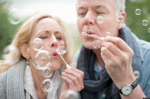 Older couple blowing bubbles in park